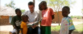 Sam in Tanzania looking at a photo album